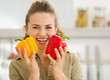 Smiling young housewife holding fresh bell peppers