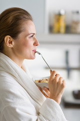 Young woman in bathrobe enjoying breakfast in morning