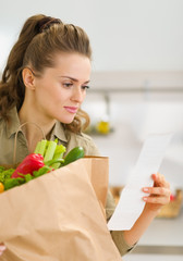 Young housewife examines check after shopping