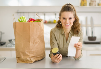 Smiling housewife examines purchases and check after shopping