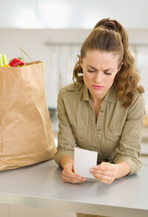 Concerned young housewife examines check after shopping