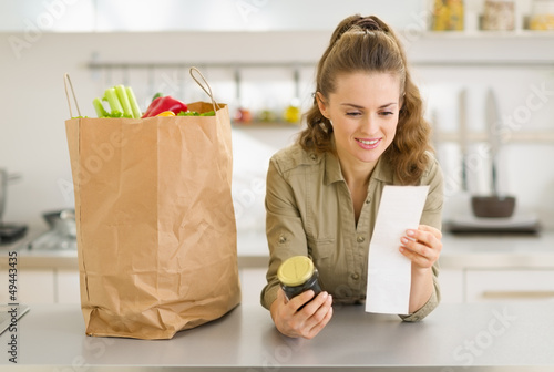 Smiling young housewife examines purchases and check after shopp