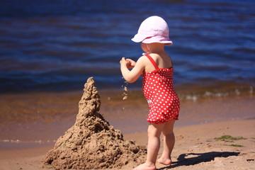 Little girl build a sandcastle