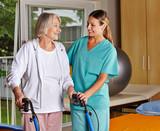 Physiotherapeutin hilft Seniorin mit Rollator