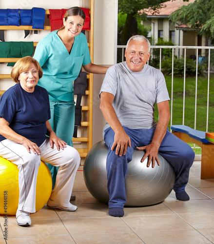 Senioren auf Gymnastikball bei Physiotherapie