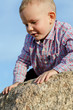 Adorable little boy climbing a rock