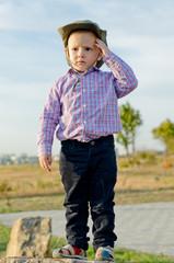 Cute little boy standing on a rock