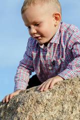Adorable little boy climbing a rock