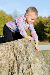 Young boy clambering on rocks