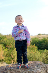 Small boy standing on a rock
