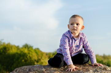 Little boy sitting on a rock