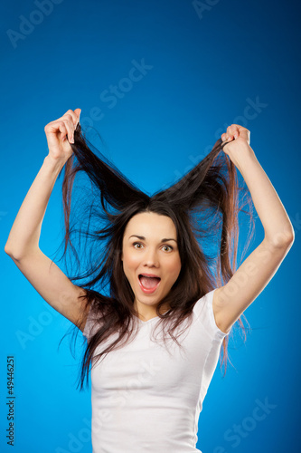 funny beautiful brunette girl holding her long hair up