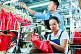 Seamstress and shift supervisor in textile factory poster