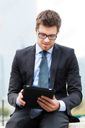 Businessman sitting on a bench and using a tablet