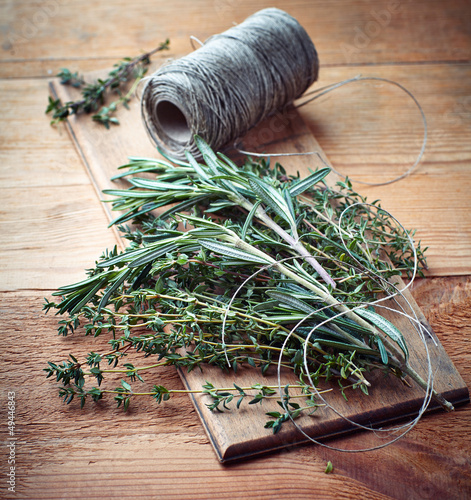 Bunch of thyme and rosemary on wooden board