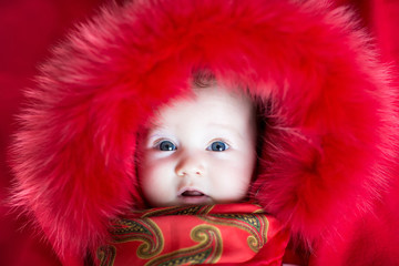 Baby girl with big blue eyes wearing a red jacket