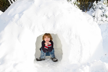 Funny boy playing in a snow igloo