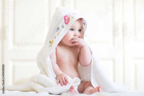 Adorable baby girl sitting under a hooded towel