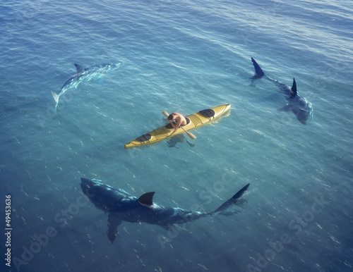 Man on a boat in the middle of the ocean surrounded by sharks.