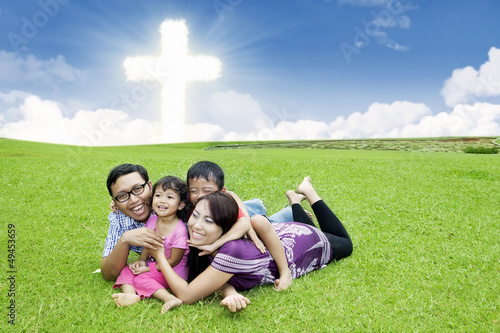 Happy Christian family on the grass