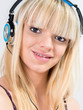 Blond Teenage girl listening to music with blue headphone