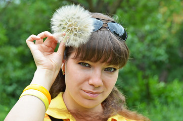 Young woman with large dandelion in hand