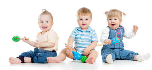 Babies playing with musical toys. Two boys and girl with maracas