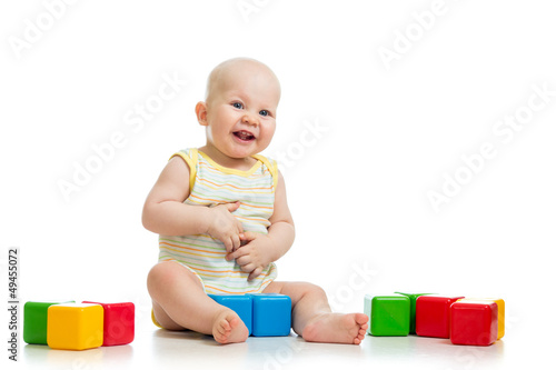 smiling child playing with colorful building blocks or bricks