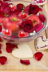 Valentine cookies, candles, rose petals and apple