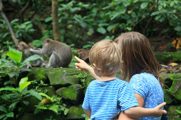 family looking at wild monkey in nature