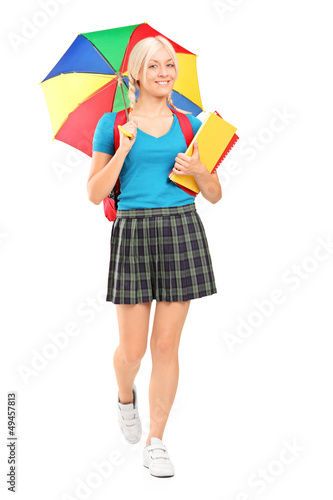 Full length portrait of a blond female student walking with umbr