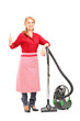 Blond housewife posing on a vacuum cleaner and giving thumb up