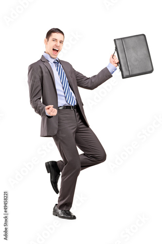 Happy businessman holding a briefcase and gesturing happiness