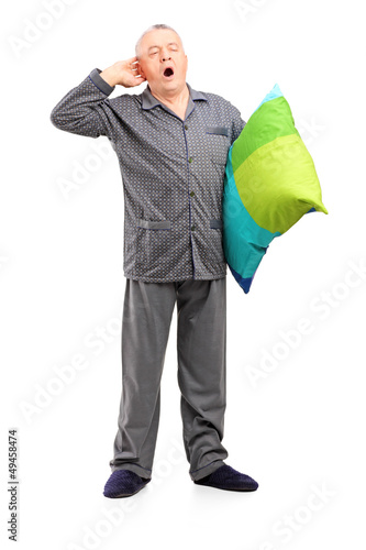 Full length portrait of a sleepy mature man in pajamas holding a