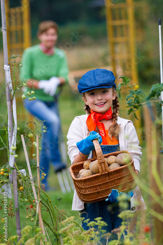 Gardening - girl helping mother in the vegetable garden