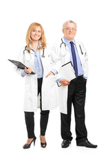 Full length portrait of a team of doctors holding a clipboard an