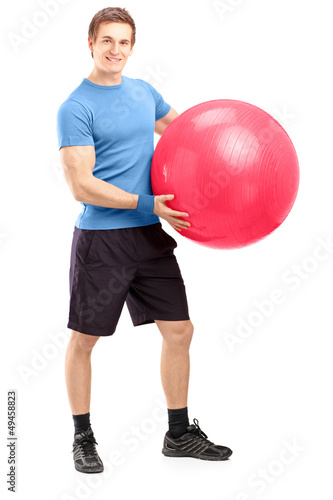 Full length portrait of a young male athlete holding a pilates b