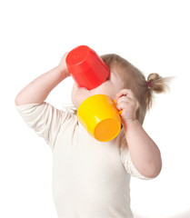 Child drinks juice from a mug.