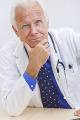 Senior Male Doctor With Stethoscope at Desk