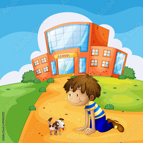 A little boy and his pet near the school