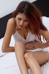 woman with menstruation pain or stomach trouble in bedroom