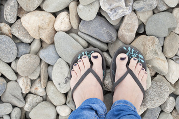 girl feet in sandals, with blue nail polish on the beach rocks