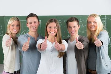 schülerteam zeigt motiviert daumen hoch