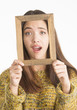 Attractive young woman holding wooden frame