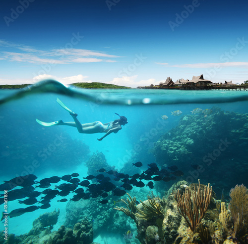 Leinwandbild Motiv Young woman snorkeling in the coral reef in the tropical sea