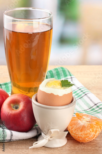Light breakfast with boiled egg and glass of juice