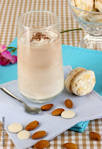 Glass of chocolate-cream cocktail on beige tablecloth close-up