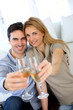 Couple holding glass of champagne towards camera