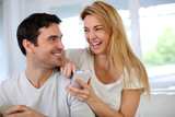 Cheerful woman showing smartphone to boyfriend