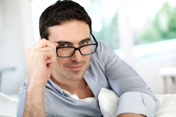 Good-looking man with eyeglasses sitting on sofa